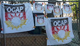 OCAP logo flags hanging from a chainlink fence