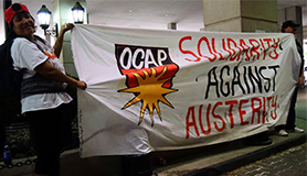OCAP members hold Solidarity Against Austerity banner in Sheraton Hotel to protest shelter for the rich but not the poor.