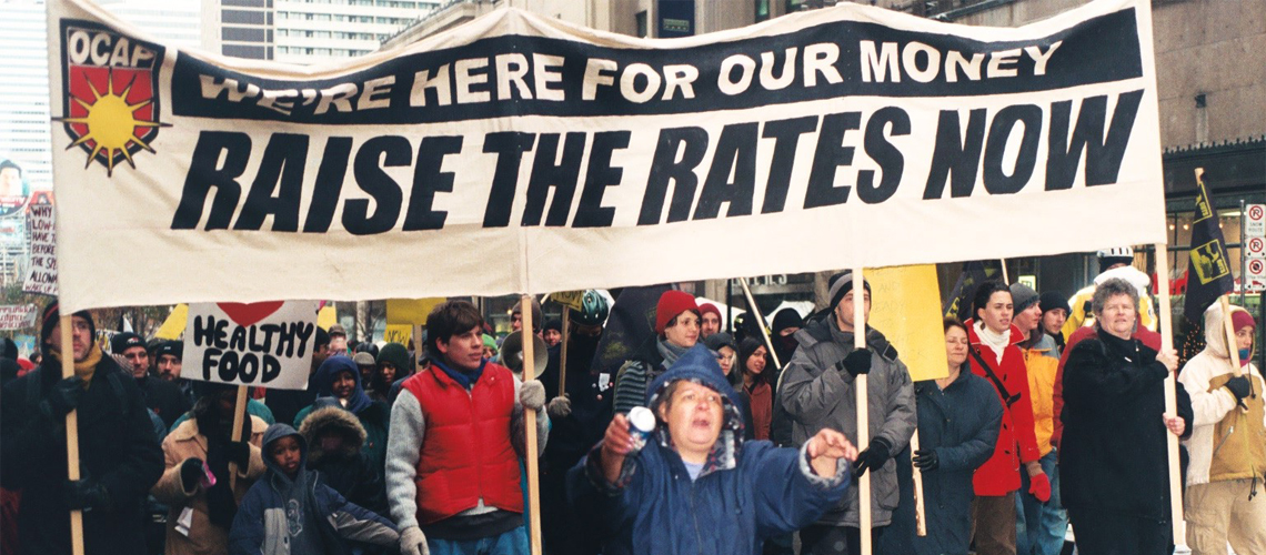"Raise the Rates march. Large crowd following behind a banner that says ""We're here for our money, Raise the Rates Now""."