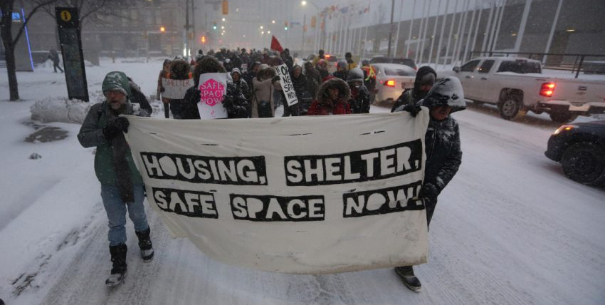 "March through a blizzard to demand shelters be opened. Front banner says ""Housing, Shelter, Safe Space Now!"""