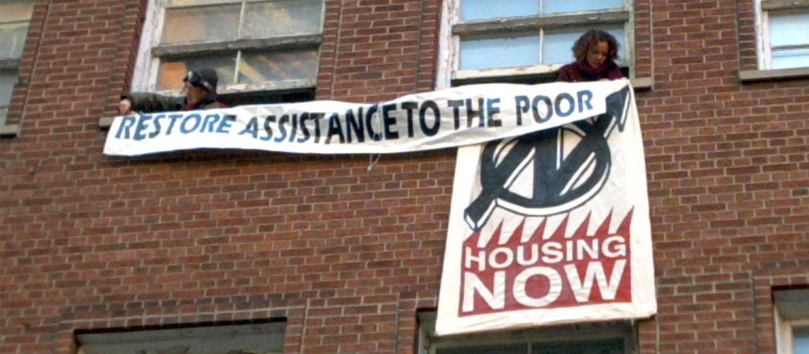 "OCAP occupation of Liberal Party headquarters to demand a raise in the rates. Banners being hung outside the windows say ""Restore assistance to the poor"" and ""housing now"""