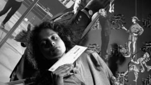 Artistic black and white photo. Woman holding up a cheque. Businessman and Robin Hood in background.
