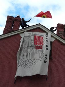 Giant Taking it Back: Housing Now banner hanging from roof of empty building at 230 Sherbourne. Above stand two Indigenous men, one waves the Unity flag.