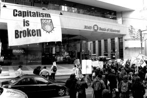 """Giant """"Capitalims is Broken"""" banner hangs from Bank of Montreal building while protestors gather below."""